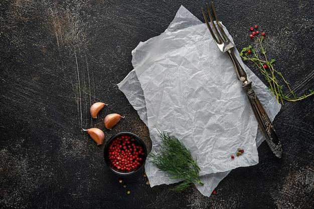 Fundo de cozinha de pedra preta. pedaço de papel pergaminho velho, especiarias e vegetais