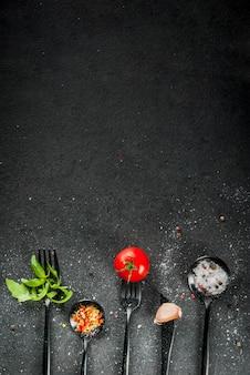 Fundo de cozinha. um conjunto de itens de mesa preto - garfos, faca e colheres com ervas frescas (manjericão, rúcula), tomate, alho e especiarias. na mesa de pedra preta. vista superior cópia espaço vertical