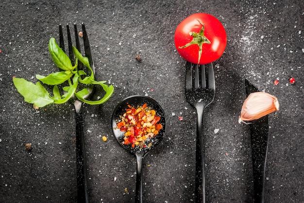 Fundo de cozinha um conjunto de itens de mesa preto - garfos faca e colheres com ervas frescas (rúcula de manjericão) tomate alho e especiarias