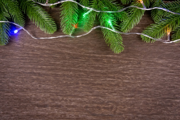 Fundo de decorações de natal com galhos de árvore do abeto e luzes de natal.