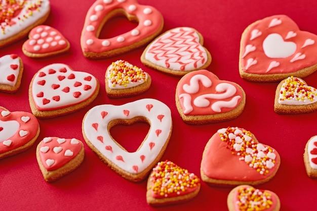 Fundo de decorado com biscoitos de forma de coração de confeiteiro sobre fundo vermelho, configuração plana. conceito de comida do dia dos namorados