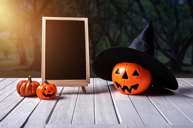 Fundo de dia das bruxas. abóbora assustadora, lousa no chão de madeira e floresta escura.