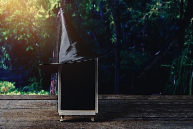 Fundo de dia das bruxas. chapéu de bruxa, lousa no chão de madeira e floresta escura.