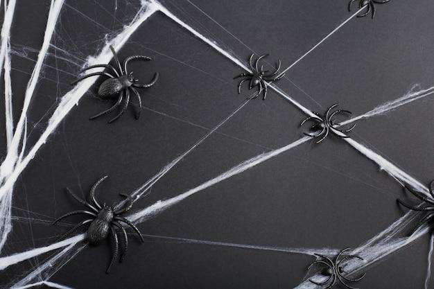 Fundo de dia das bruxas com aranhas e teia de aranha em fundo preto. decorações do feriado de halloween. camada plana, vista superior, espaço de cópia.