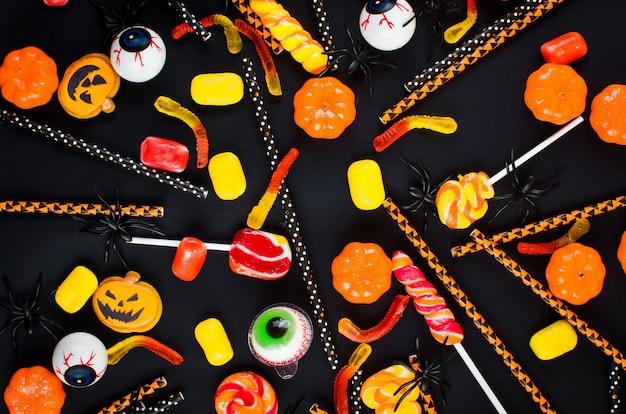 Fundo de dia das bruxas com biscoitos de gengibre, abóbora, doces em fundo preto, espaço de cópia, vista superior, disposição plana, maquete