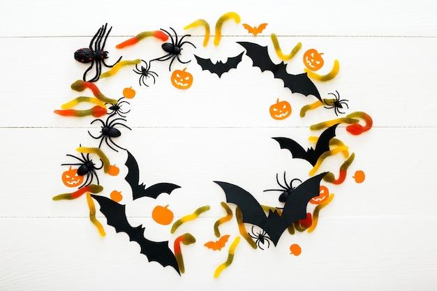 Fundo de dia das bruxas com doce doce, minhocas, morcegos de papel, aranhas, abóboras papar em fundo branco de madeira. decorações do feriado de halloween. camada plana, vista superior, espaço de cópia. quadro, armação