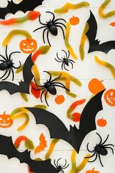 Fundo de dia das bruxas com doce doce, minhocas, morcegos de papel, aranhas, abóboras papar em fundo branco de madeira. decorações do feriado de halloween. camada plana, vista superior, espaço de cópia