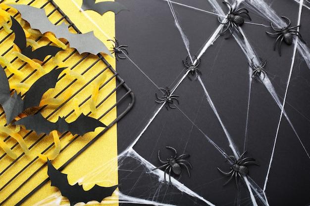 Fundo de dia das bruxas com doce doce, vermes, morcegos de papel, aranhas e teia de aranha em fundo preto e amarelo glitter. decorações do feriado de halloween. camada plana, vista superior.