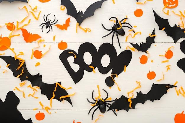 Fundo de dia das bruxas com jack-o'-lanter, abóboras, morcegos de papel, aranhas, confetes em fundo branco de madeira. decorações do feriado de halloween. camada plana, vista superior. maquete de convite de festa, celebração.