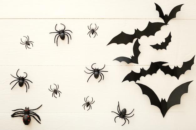 Fundo de dia das bruxas com morcegos de papel, abóboras, aranhas em fundo branco de madeira. decorações do feriado de halloween. camada plana, vista superior, espaço de cópia. maquete de convite de festa, celebração