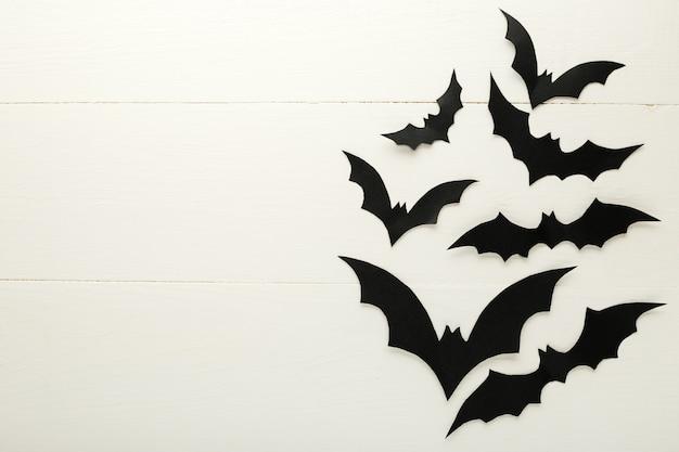 Fundo de dia das bruxas com morcegos de papel em fundo branco de madeira. quadro, armação. decorações do feriado de halloween. camada plana, vista superior, espaço de cópia. maquete de convite de festa, celebração.