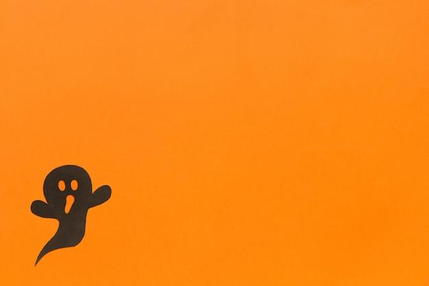 Fundo de dia das bruxas fantasma de papel preto sobre fundo laranja