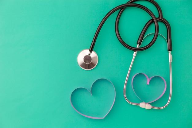 Fundo de dia de saúde do mundo, estetoscópio e coração de fita rosa sobre fundo verde, cuidados de saúde de conceito e formação médica