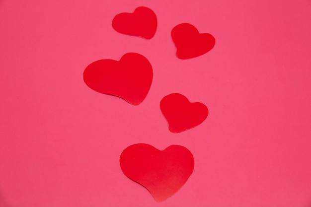 Fundo de dia dos namorados com cinco corações em fundo rosa