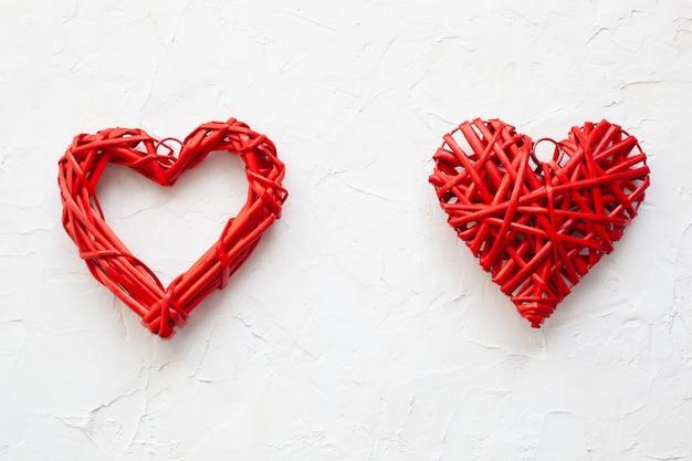 Fundo de dia dos namorados com corações. corações de madeira vermelhos do amor no fundo branco. conceito de amor medicina, doença cardíaca. decoração de casa rústica para férias. forma de corações. cartão de dia dos namorados.