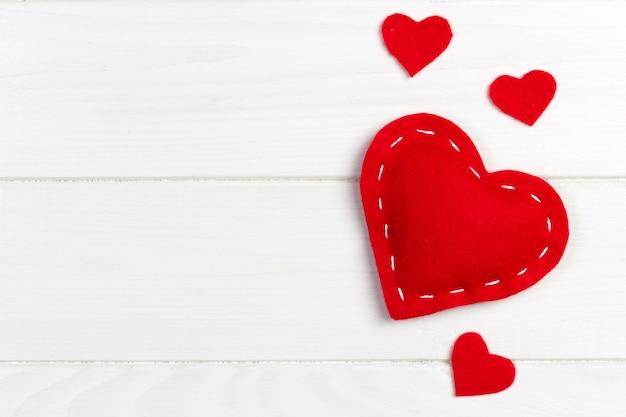 Fundo de dia dos namorados com corações de têxteis estampados em fundo de madeira