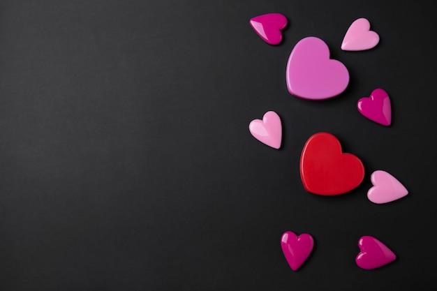 Fundo de dia dos namorados com corações rosa e vermelhos em fundo de espaço preto cópia.