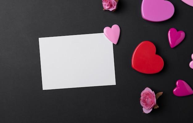 Fundo de dia dos namorados com corações vermelhos e cartão em fundo preto espaço de cópia.