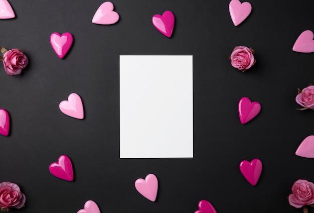 Fundo de dia dos namorados com corações vermelhos e cartão postal em fundo preto.