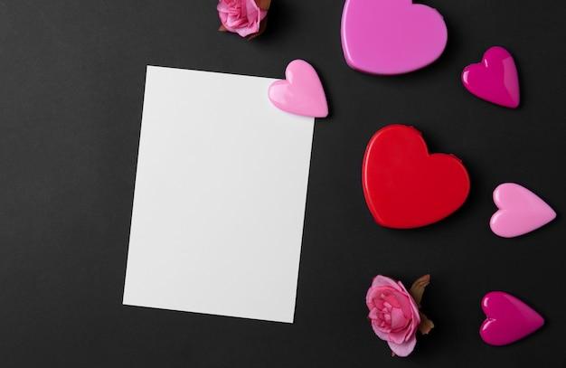 Fundo de dia dos namorados com corações vermelhos e cartão postal em preto cópia espaço plano de fundo.