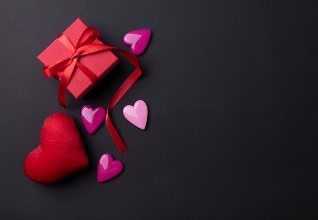 Fundo de dia dos namorados com corações vermelhos e presente em fundo preto espaço de cópia.