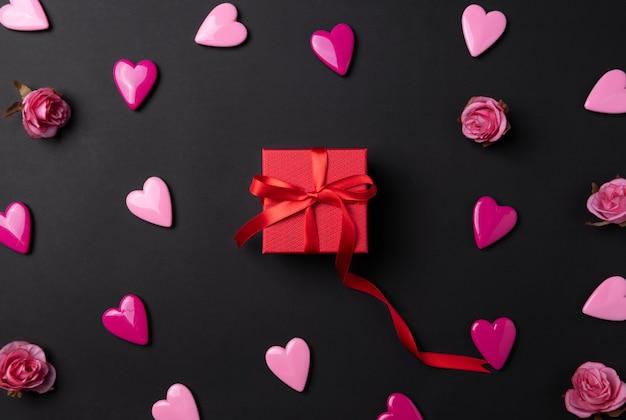 Fundo de dia dos namorados com corações vermelhos e presente em fundo preto.