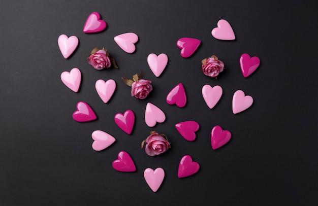 Fundo de dia dos namorados com corações vermelhos e rosa em fundo preto.