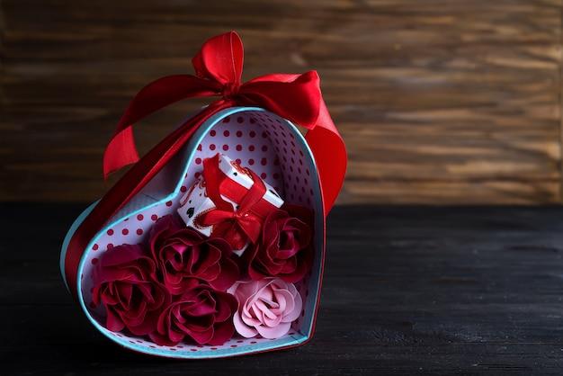 Fundo de dia dos namorados com corações vermelhos e rosa na caixa de presente no fundo escuro de madeira