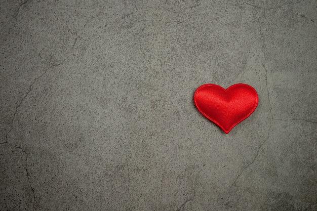 Fundo de dia dos namorados com corações vermelhos na velha mesa de concreta
