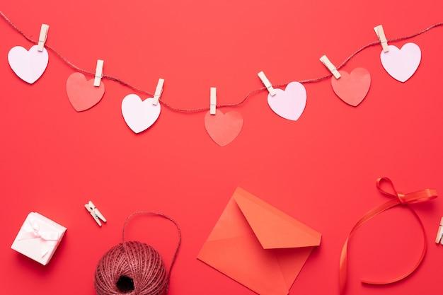 Fundo de dia dos namorados com decorações de forma de coração, presente e fitas. vista de cima. composição plana leiga