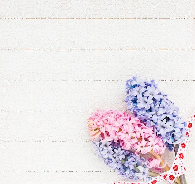 Fundo de dia dos namorados com jacintos na mesa de madeira branca.