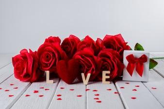 Fundo de dia dos namorados com rosa vermelha, forma de coração, caixa de presente, palavra de letras de madeira