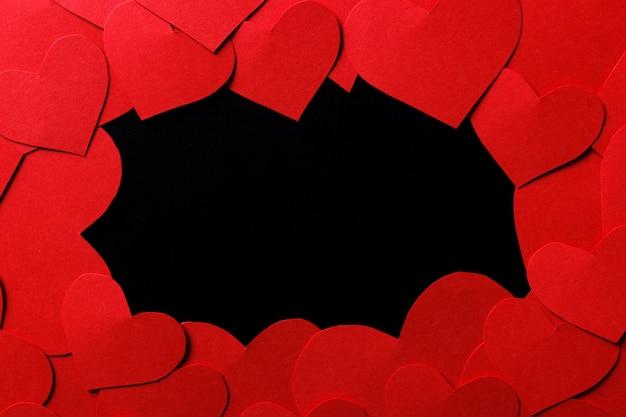 Fundo de dia dos namorados. corações de papel vermelho na mesa de madeira preta com copyspace