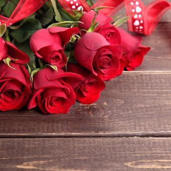 Fundo de dia dos namorados de rosas vermelhas e fita na madeira