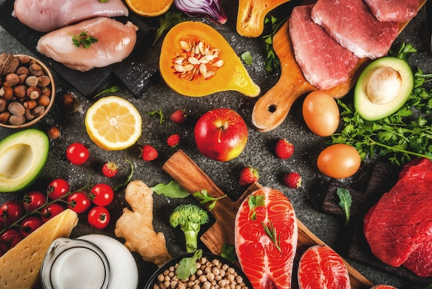 Fundo de dieta saudável. ingredientes de alimentos orgânicos, superalimentos: carne bovina e suína, filé de frango, peixe salmão, feijão, nozes, leite, ovos, frutas, legumes. mesa de pedra preta, copyspace vista superior
