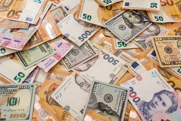 Fundo de dinheiro de notas de euros e hryvnia de dólares de diferentes países. conceito de finanças