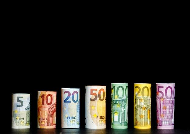 Fundo de dinheiro do euro. várias centenas de rolos de notas de euro em posições diferentes.