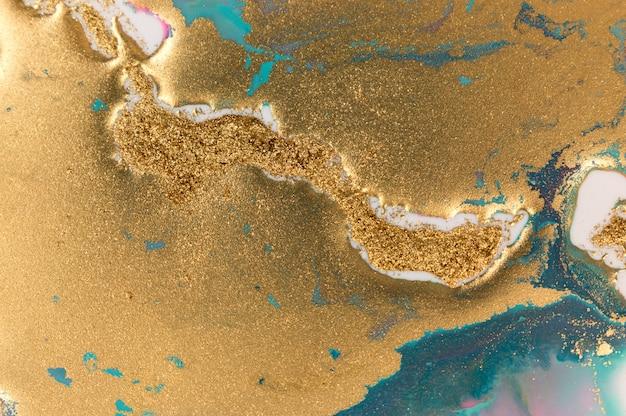 Fundo de dispersão de glitter dourado. ouro cintilante e textura azul.