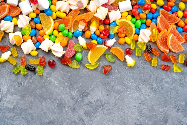 Fundo de doces e balas. doces diferentes, marshmallows, geleias, yummi gummi espalhados sobre a mesa. vista do topo.