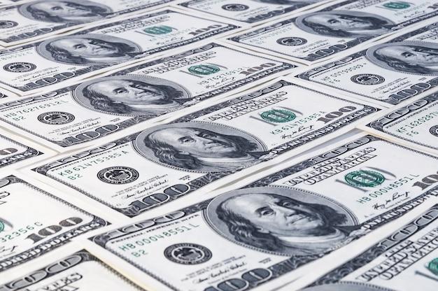 Fundo de dólares. notas de cem dólares americanos estão espalhadas pelo fundo.