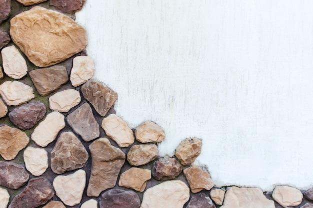 Fundo de duas partes: textura de pedras grandes e gesso branco.