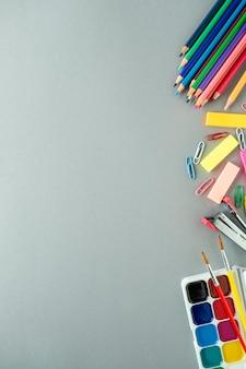 Fundo de educação com espaço de texto. material escolar em fundo cinza. vista do topo