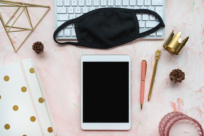 Fundo de escritório em casa. máscara e teclado em rosa