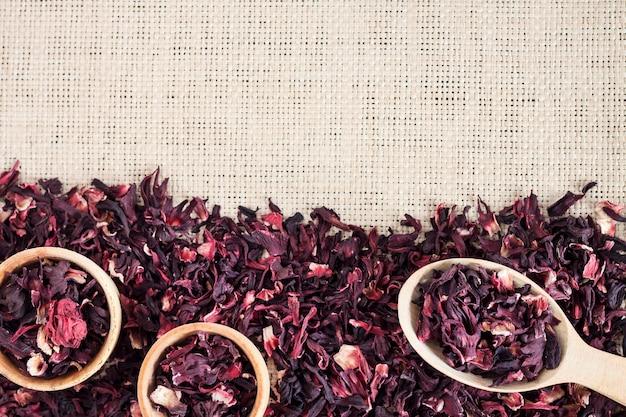 Fundo de esteira de palha com chá de hibisco colher de pau com pétalas de hibisco secas