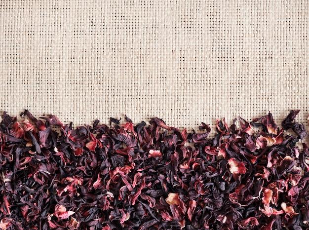 Fundo de esteira de palha com chá de hibisco seco, closeup. camada plana, vista superior.