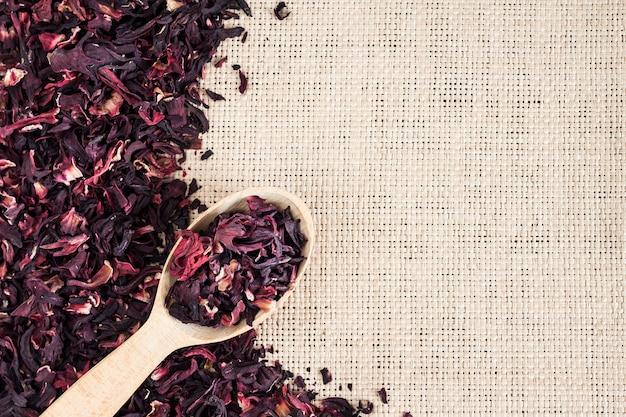Fundo de esteira de palha com chá de hibisco seco e colher de pau com chá de hibisco