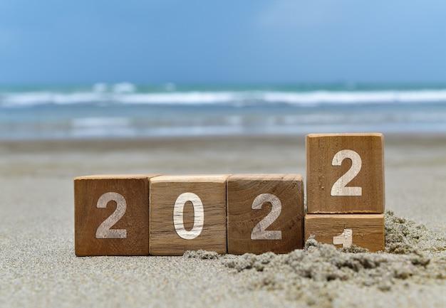 Fundo de feliz ano novo de 2022 com cubo de madeira na praia