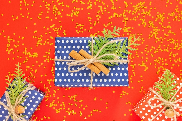 Fundo de férias, caixas de presente vermelhas e azuis em bolinhas com fita e arco e galhos de thuja em um fundo vermelho com estrelas douradas brilhantes, lay-out plana, vista de cima