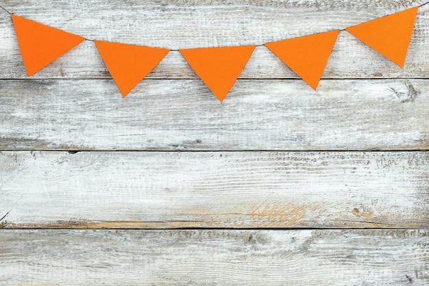 Fundo de férias com pequenas bandeiras laranja penduradas em uma superfície de madeira
