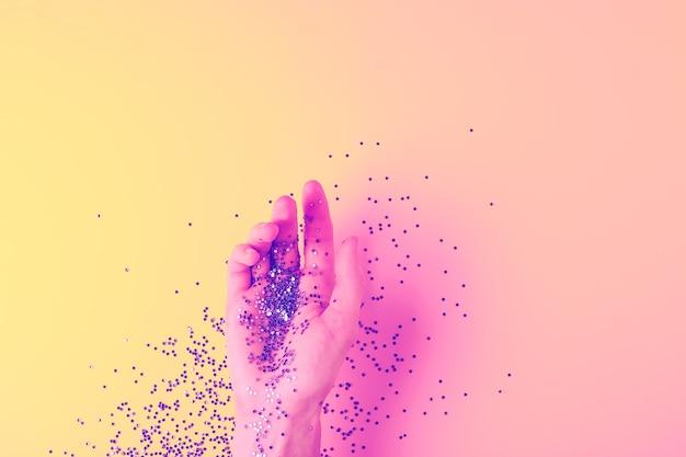 Fundo de férias criativas em luz de néon com a mão de uma mulher segurando confetes